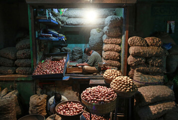 A vendor works at his vegetable stall at a wholesale fruit and vegetable market in Mumbai