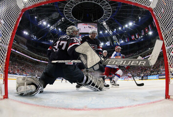Goaltender Hellebuyck of the U.S. makes a save past Moore and Russia's Mozyakin during their Ice Hockey World Championship semifinal game at the O2 arena in Prague