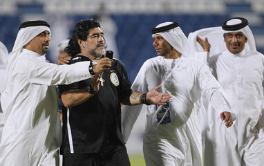 Fans of Qatar's Al Khor take a photo with Argentine football legend Diego Maradona and coach of UAE's Al-Wasl after their GCC Champions League soccer match in Doha