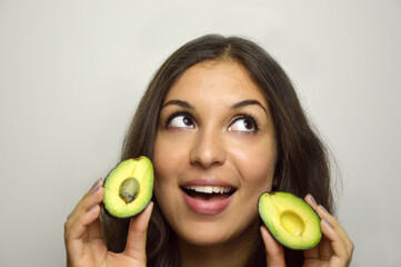 Portrait of attractive girl with avocado healthy fruit