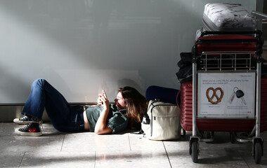 A woman waits with her luggage at Heathrow Terminal 5 in London