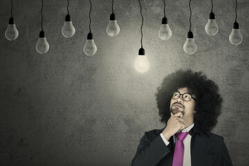 Afro businessman looking at light bulb