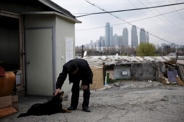 A man pats his dog as a luxury high-rise apartment complex is seen in the background at Guryong village in Seoul