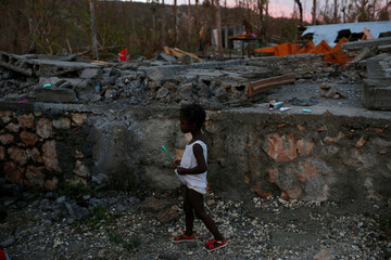 A girl walks next to a partially destroyed school used as a shelter after Hurricane Matthew hit Jeremie