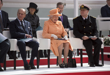 "Britain's Queen Elizabeth and Prince Philip sit with Captain Paul Brown during the christening ceremony of P&O's new cruise liner ""Britannia"" in Southampton"