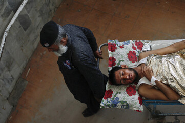 Hospital security transports on a stretcher a man as he receives treatment at Lady Reading hospital in Peshawar