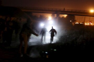Migrants are illuminated by police torches as they run to cross a fence during an attempt to access the Channel Tunnel in Frethun, near Calais