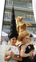 Models wearing hats designed from hair in shapes of Burj Khalifa and horse, pose ahead of 17th Dubai World Cup at Meydan racecourse in Dubai