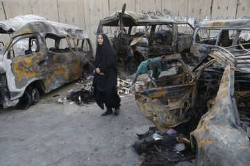 A woman looks at vehicles destroyed in a car bomb attack in the Shaoula neighbourhood of Baghdad