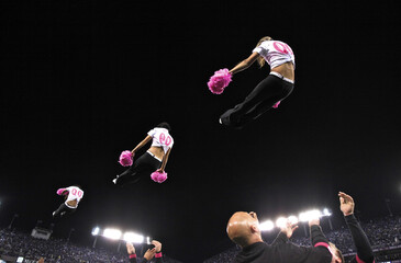 Baltimore Ravens cheerleaders perform a stunt during a Ravens NFL football game in Baltimore