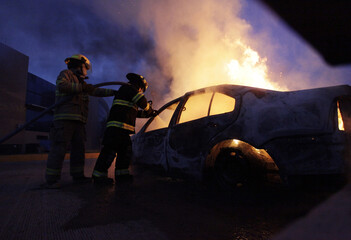 Firefighters extinguish fire on a car after a protest in support of the missing students of Ayotzinapa Teacher Training College Raul Isidro Burgos outside the government palace of Guerrero state in Chilpacingo