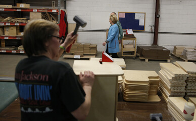 Worker assembles furniture as U.S. presidential candidate and former Secretary of State Hillary Clinton tours children's toy and furniture factory while campaigning in Keene, New Hampshire