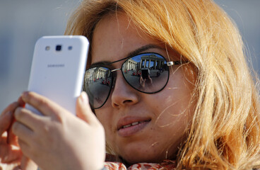 A tourist takes pictures with her mobile phone as Berlin's landmark Brandenburg Gate is reflected in her sunglasses during a sunny spring day in Berlin