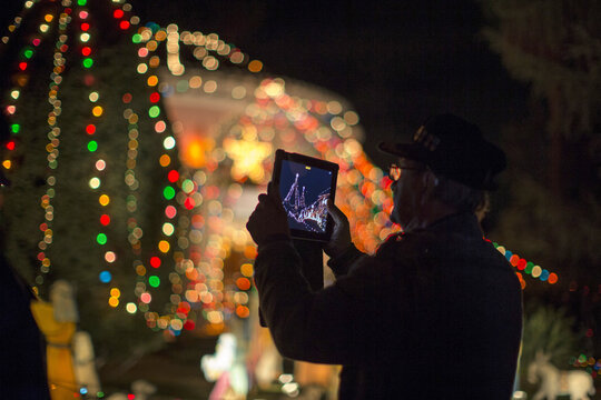 A person uses a tablet in front of the Balian Ice Cream House which is decorated for Christmas in Altadena
