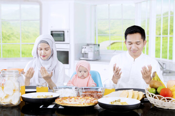 Happy family praying together in kitchen