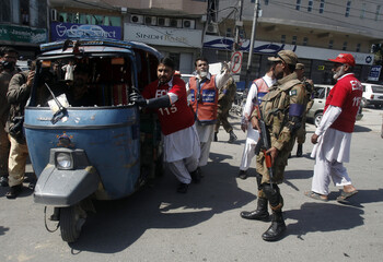 A soldier stands guard as rescue workers remove an auto-rickshaw form the site of a bomb blast in Peshawar