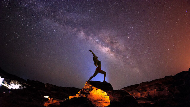 Landscape with Milky way galaxy. Night sky with stars and silhouette woman practicing yoga on the mountain.