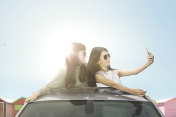 Young women taking selfie photo on car sunroof