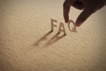 FAQ wood word on compressed board,corkboard with human's finger at Q letter