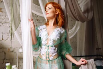 Tender redhead woman in transparent mint peignoir