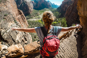Hiker with backpack stands on the edge with raised hands and looks at the valley