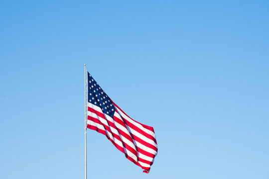 American Flag Against Cloudless Sky Unfurled in the Wind. Image has copy space.