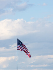 Vertical photo of American Flag against gray and white cumulus clouds and blue sky. The flag is unfurled in the breeze.