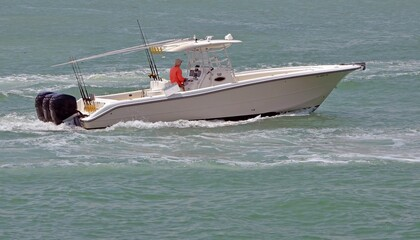 Fishing boat powered bt three outboard engines cruising on the florida intra-coastal waterway off Miami Beach.