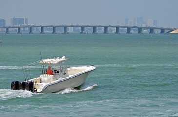 Sport fishing boat powered by three outboard engines cruising on the florida inter-coastal waterway with a Julia Tuttle Causeway bridge connecting Miami with Miami Beach in the background.
