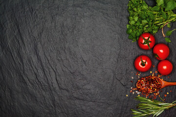 Sea salt, tomatoes and fresh organic basil. Ingredients for cooking. Food background on black slate table. Top view copy space.