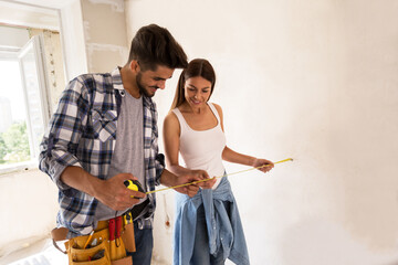 Lovely couple with tape measure, renovation concept