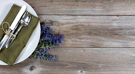 Vintage dinnerware on rustic wooden table with flowers