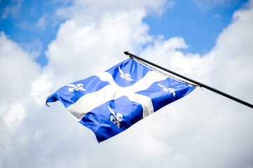 The waving flag of Quebec against the blue sky