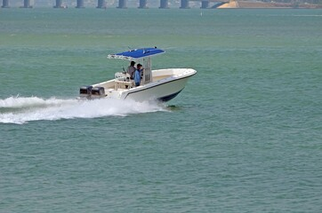 Small fishing boat p;owe red by two outboard engines speeding across the florida intra-coastal waterway off Miami Beach,