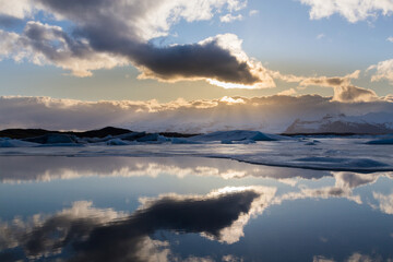 Reflection winter lagoon with sun behind white clouds, Iceland winter natural landscape background
