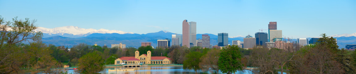 Extremely large format 55 inches wide panorama of downtown Denver skyline buildings, on a bright clear summer morning with lake and trees in foreground and snow capped mountains in background.