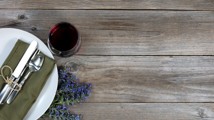 Vintage dinnerware on rustic wooden table with flowers and a glass of red wine