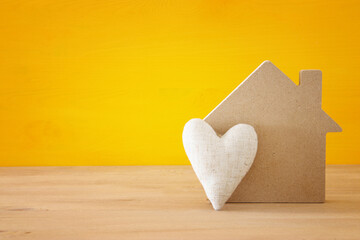Wooden house model with next to heart on old table