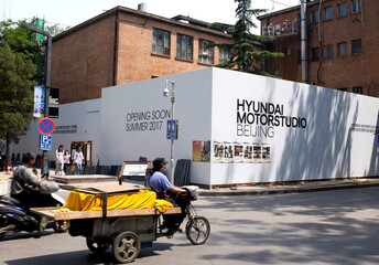 A tricycle drives past the construction site of the Hyundai Motor Studio in Beijing