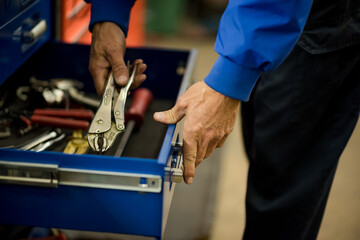 hands on tools in a large blue toolbox auto repair technician