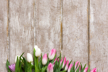 Frame of pink tulips on wooden background. Flower bouquet in florist workplace with copyspace. Wedding, gift, birthday, 8 march, mother's day greeting card concept