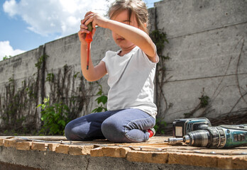 little girl repairing with screwdriver and screwdriver in hand