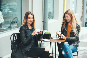 Two beautiful attractive stylish women are sitting outdoor in cafe drinking coffe and tea talking and enjoying great day. Concept of friendship people rest fashion study communication activity