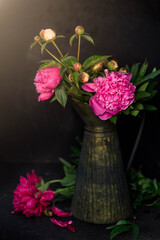 Peonies in an iron vase against a beautiful sunset