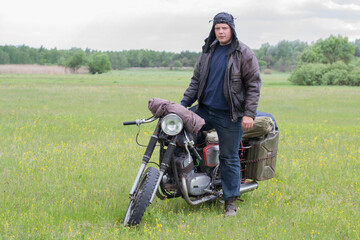 A post apocalyptic man on motorcycle in a meadow