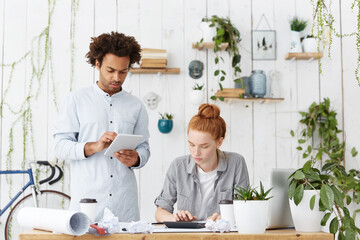 Team work of hard-working architect workers. Attractive male with trendy hairdo holding tablet and pretty redhead woman dressed in casual clothes making calculations isolated over home cozy interior