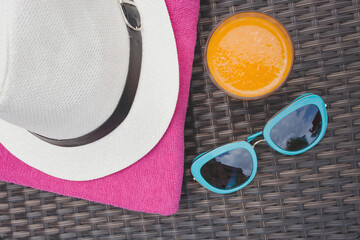 Summertime orange juice hat and sunglasses relax near swimming pool