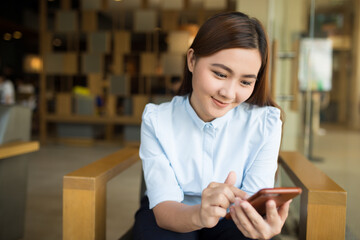 Happy woman using smartphone in cafe