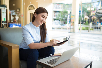 Happy woman using tablet with laptop in cafe