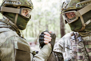 Soldiers shaking hands in woods